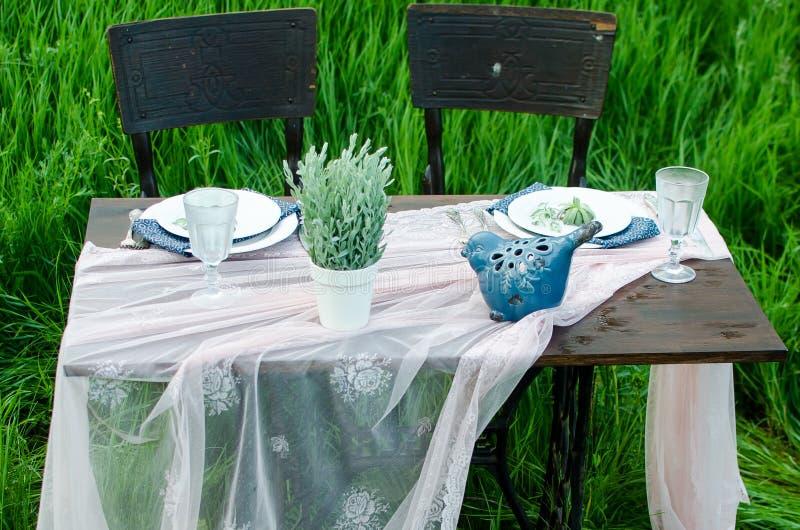 Πίνακας γαμήλιων διακοσμήσεων στο αγροτικό ύφος στην πράσινη χλόη Κλείστε επάνω του σκοτεινού ξύλινου πίνακα, του άσπρου τραπεζομ στοκ φωτογραφίες