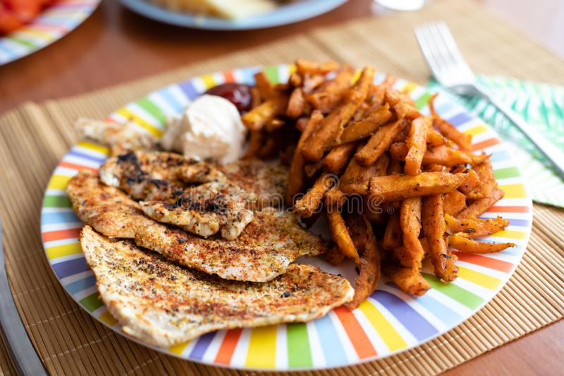 Πίνακας γευμάτων με το ζωηρόχρωμο πιάτο με το στήθος κοτόπουλου και τις γλυκές πατάτες στοκ φωτογραφίες με δικαίωμα ελεύθερης χρήσης