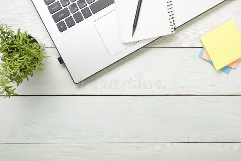 Πίνακας γραφείων γραφείων με τις προμήθειες Τοπ όψη Διάστημα αντιγράφων για το κείμενο Lap-top, σημειωματάριο, μάνδρα και λουλούδ στοκ φωτογραφίες