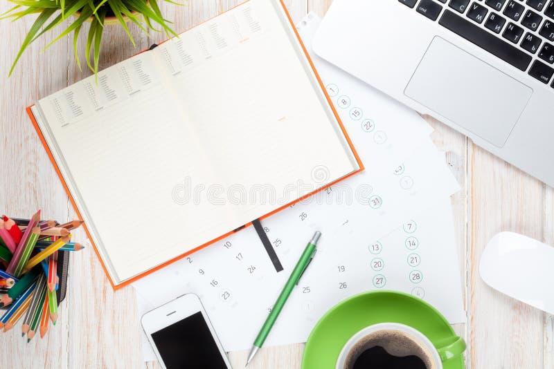 Πίνακας γραφείων γραφείων με τον υπολογιστή, τις προμήθειες, το φλυτζάνι καφέ και το λουλούδι στοκ φωτογραφία