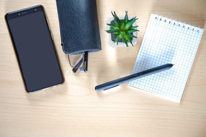 Πίνακας γραφείων Smartphone, γυαλιά σε έναν διακοσμητικό κάκτο περίπτωσης, σημειωματάριων και μανδρών Ξύλινος πίνακας στοκ εικόνες