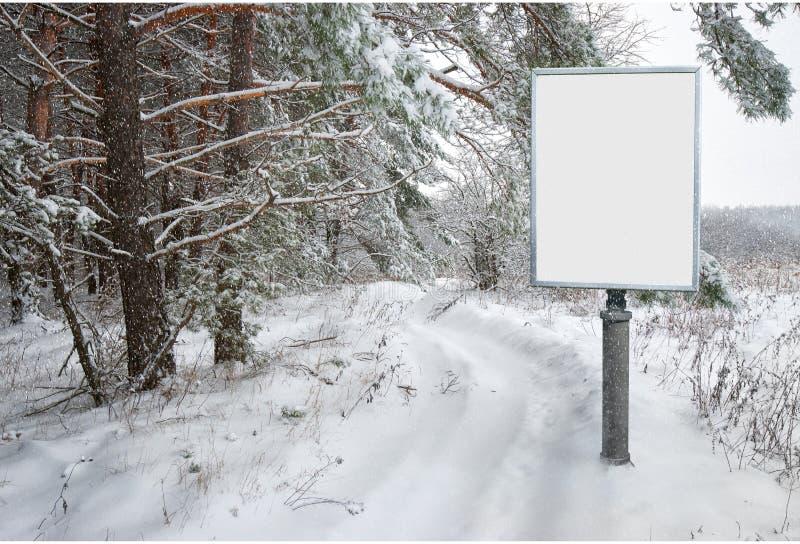 Πίνακας διαφημίσεων για τη διαφήμιση στο υπόβαθρο του χιονώδους δασικού τοπίου στοκ φωτογραφία
