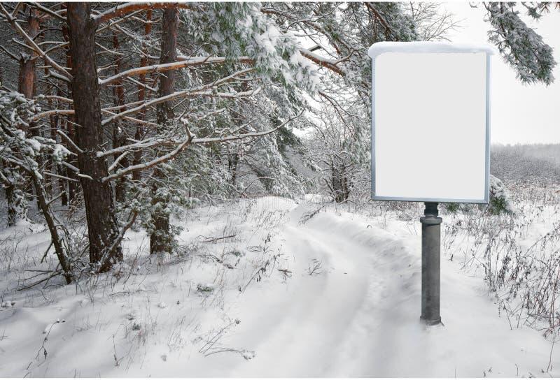 Πίνακας διαφημίσεων για τη διαφήμιση στο υπόβαθρο του χιονώδους δασικού τοπίου στοκ φωτογραφίες με δικαίωμα ελεύθερης χρήσης