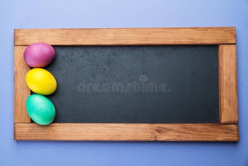 Πίνακας και ζωηρόχρωμα αυγά Πάσχας γύρω από το επάνω από την όψη στοκ φωτογραφία με δικαίωμα ελεύθερης χρήσης