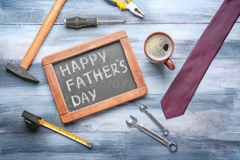Πίνακας κιμωλίας με ευτυχής πατέρας \ «s κειμένων \ «ημέρα \», δεσμός, εργαλεία και φλιτζάνι του καφέ στο ξύλινο υπόβαθρο στοκ φωτογραφίες με δικαίωμα ελεύθερης χρήσης