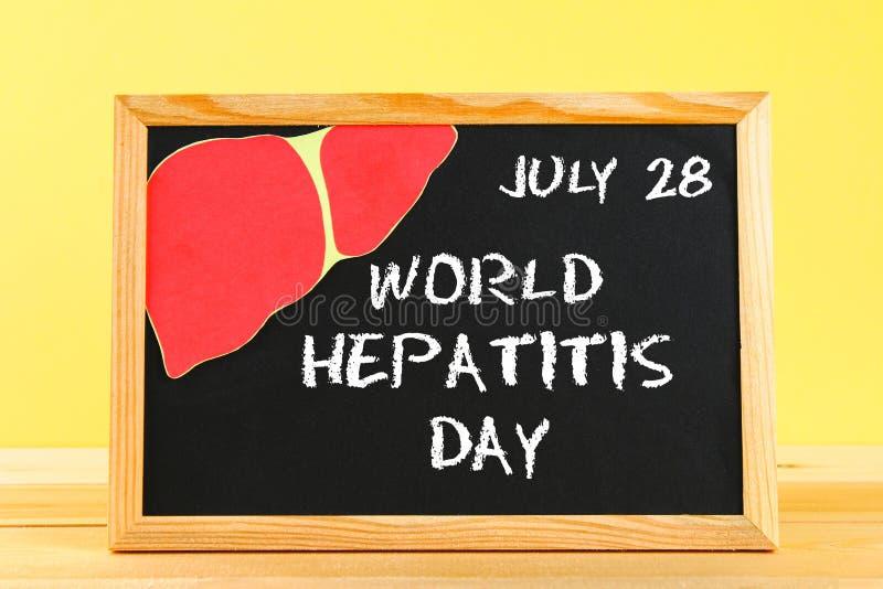 Πίνακας κιμωλίας με την ημέρα παγκόσμιας ηπατίτιδας κειμένων 28 Ιουνίου Συκώτι σε έναν ξύλινο πίνακα σε ένα κίτρινο κλίμα τοίχων στοκ εικόνες