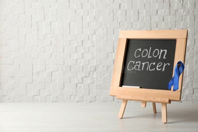 Πίνακας κιμωλίας με την μπλε συνειδητοποίηση καρκίνος του παχέος εντέρου κορδελλών και κειμένων στοκ φωτογραφία