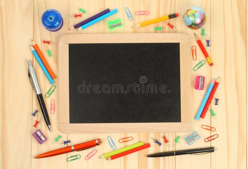 Πίνακας κιμωλίας με τις προμήθειες σχολικών γραφείων στοκ εικόνες
