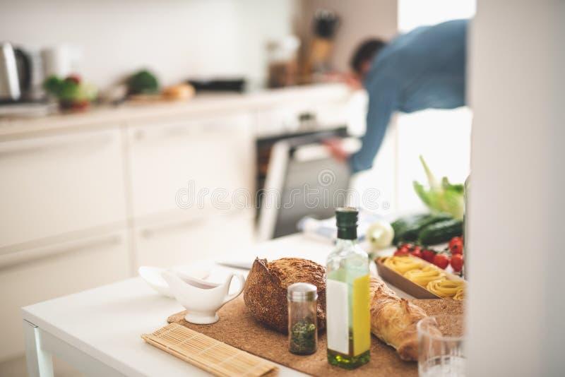 Πίνακας με τα συστατικά για το μαγείρεμα και νεαρός άνδρας στο θολωμένο υπόβαθρο στοκ εικόνα με δικαίωμα ελεύθερης χρήσης