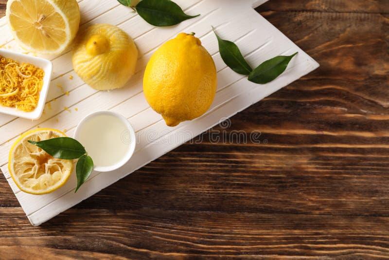 Πίνακας με τα ώριμα λεμόνια, την απόλαυση και το φρέσκο χυμό στον ξύλινο πίνακα στοκ φωτογραφίες με δικαίωμα ελεύθερης χρήσης