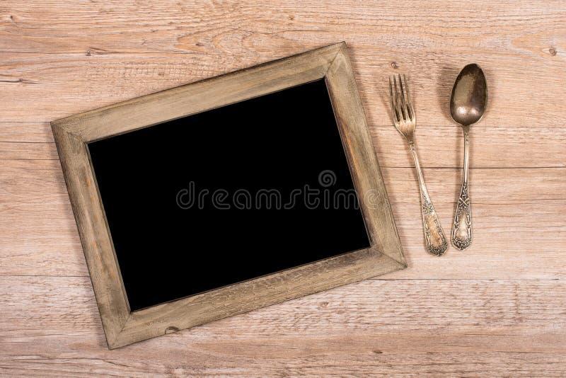 Πίνακας με το πλαίσιο του ξύλου και του δικράνου και του κουταλιού στοκ εικόνες