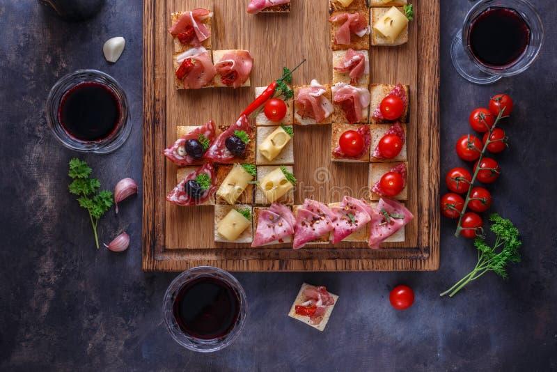 Πίνακας ορεκτικών με τα ιταλικά πρόχειρα φαγητά antipasti και κρασί στα γυαλιά Brushetta ή αυθεντικά παραδοσιακά ισπανικά tapas κ στοκ εικόνα με δικαίωμα ελεύθερης χρήσης