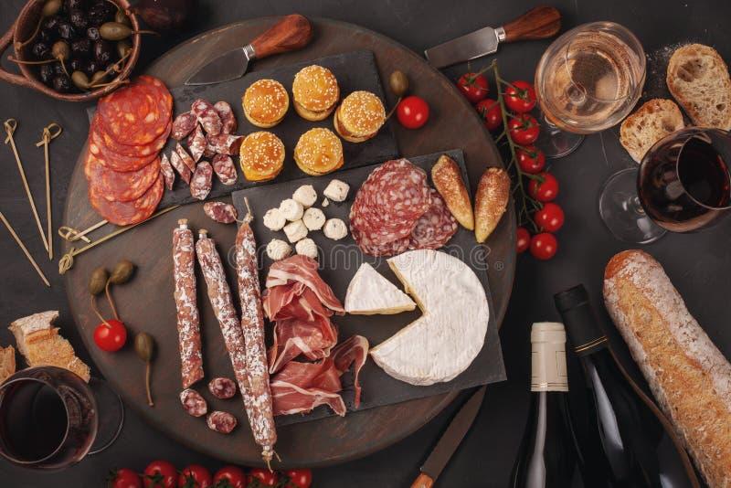 Πίνακας ορεκτικών με το antipasti, το τυρί, charcuterie, τα πρόχειρα φαγητά και το κρασί differents Μίνι burgers, λουκάνικο, ζαμπ στοκ φωτογραφία με δικαίωμα ελεύθερης χρήσης