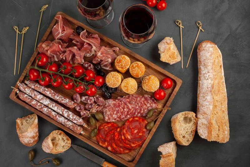 Πίνακας ορεκτικών με το antipasti, το τυρί, charcuterie, τα πρόχειρα φαγητά και το κρασί differents Μίνι burgers, λουκάνικο, ζαμπ στοκ φωτογραφίες