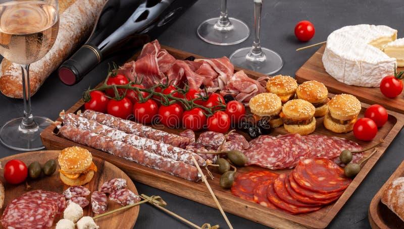Πίνακας ορεκτικών με το antipasti, το τυρί, charcuterie, τα πρόχειρα φαγητά και το κρασί differents Μίνι burgers, λουκάνικο, ζαμπ στοκ φωτογραφίες με δικαίωμα ελεύθερης χρήσης