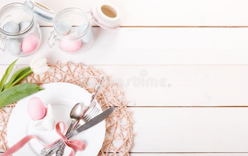 Πίνακας Πάσχας που θέτει με τα ρόδινα και μπλε αυγά και τα μαχαιροπήρουνα στο λευκό Ανασκόπηση διακοπών σκηνικό με το διάστημα αν στοκ εικόνες