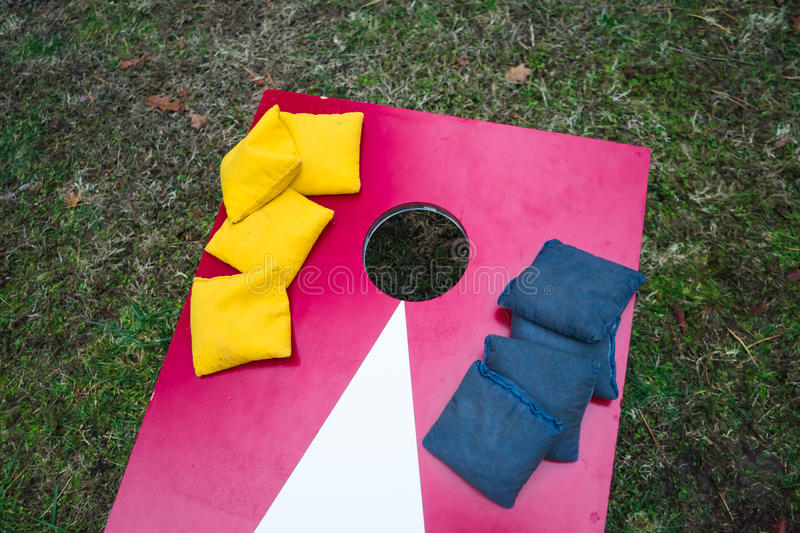 Πίνακας παιχνιδιών Cornhole με τις συσσωρευμένες τσάντες φασολιών στοκ εικόνες