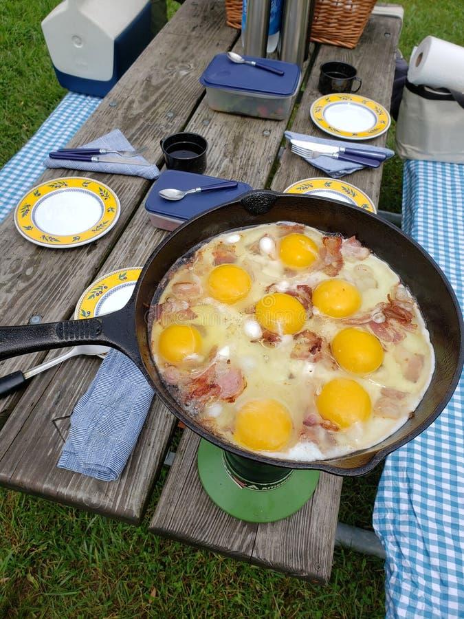 Πίνακας πικ-νίκ με ένα τηγανίζοντας παν μαγειρεύοντας μπέϊκον και τα αυγά στοκ φωτογραφία με δικαίωμα ελεύθερης χρήσης