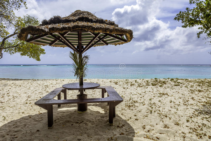 Πίνακας πικ-νίκ με την ομπρέλα αχύρου στην τροπική παραλία στοκ εικόνες