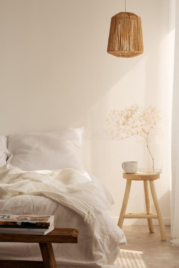 Πίνακας πλευρών με την κούπα και λουλούδι δίπλα στο κρεβάτι, πραγματική φωτογραφία με το διάστημα αντιγράφων στοκ φωτογραφία με δικαίωμα ελεύθερης χρήσης