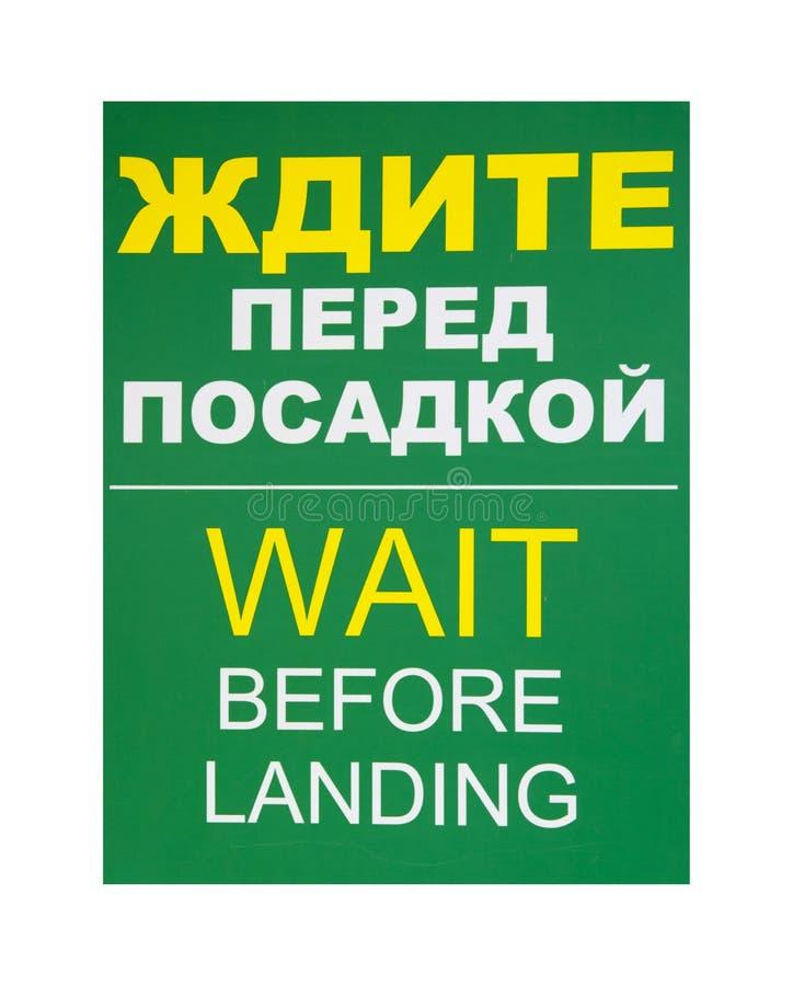 Πίνακας πληροφοριών για να περιμένει πρίν προσγειώνεται στα ρωσικά και αγγλικά στοκ εικόνα με δικαίωμα ελεύθερης χρήσης