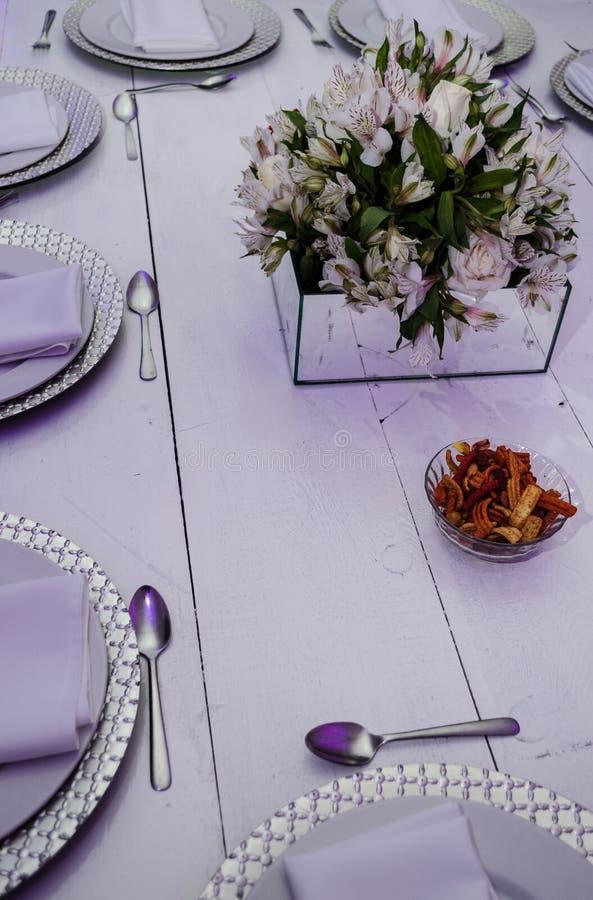 Πίνακας που διακοσμείται με τα στρογγυλά πιάτα, μια φυσική ρύθμιση λουλουδιών σε έναν άσπρο ξύλινο πίνακα, υπόβαθρο για τις παρου στοκ φωτογραφία