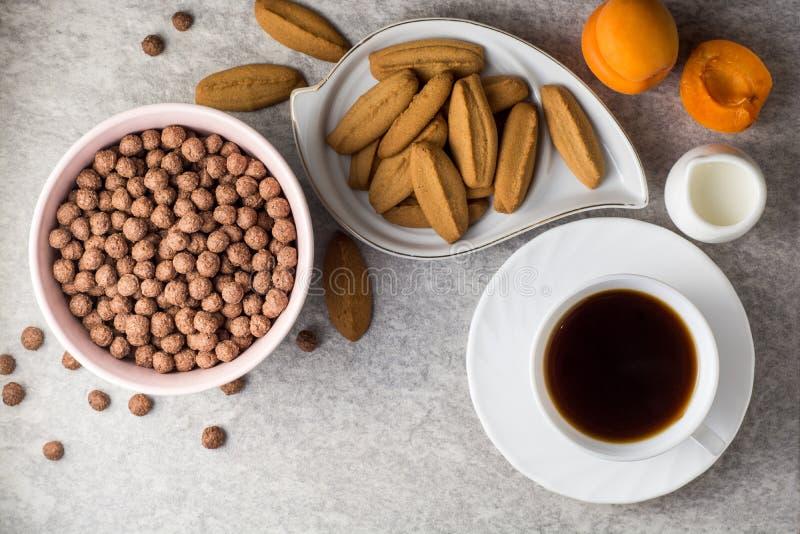 Πίνακας προγευμάτων με τον καφέ, τα μπισκότα πιπεροριζών, τις σφαίρες δημητριακών σοκολάτας, το γάλα, και τα βερίκοκα στο υπόβαθρ στοκ φωτογραφία με δικαίωμα ελεύθερης χρήσης