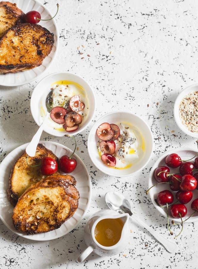 Πίνακας προγευμάτων Το ελληνικό γιαούρτι με τα κεράσια και το μέλι και η καραμέλα γαλλικά ψήνουν στον άσπρο πίνακα, τοπ άποψη Επί στοκ εικόνες