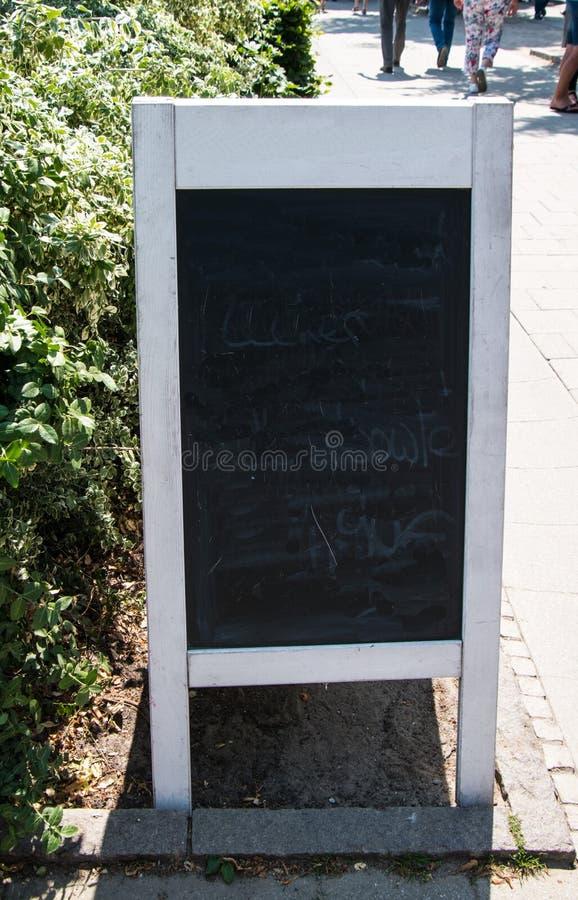 Πίνακας σημαδιών σάντουιτς με το άσπρο ξύλινο πλαίσιο Ο πίνακας παρουσιάζει σκιές της σβημένης άσπρης κιμωλίας στοκ εικόνα