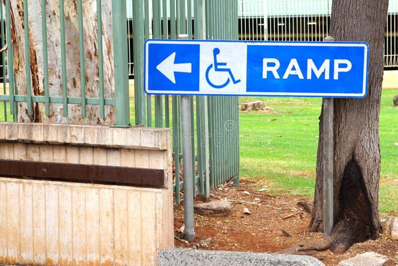 Πίνακας σημαδιών και ένα σύμβολο για μια κεκλιμένη ράμπα αναπηρικών καρεκλών στοκ φωτογραφίες