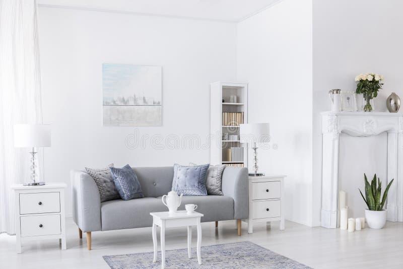 Πίνακας στον τάπητα μπροστά από τον γκρίζο καναπέ στο άσπρο εσωτερικό καθιστικών με τους λαμπτήρες και την αφίσα Πραγματική φωτογ στοκ φωτογραφία
