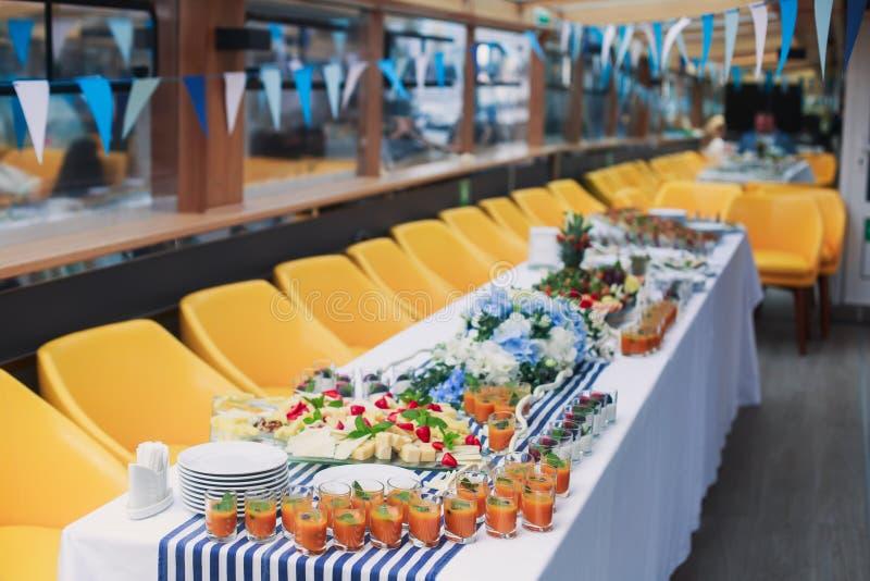 Πίνακας συμποσίου τομέα εστιάσεως με τα διαφορετικά πρόχειρα φαγητά και τα ορεκτικά τροφίμων στο εταιρικό γεγονός γιορτών γενεθλί στοκ φωτογραφία
