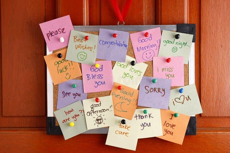 Πίνακας φελλού με τα μηνύματα σε ζωηρόχρωμα χαρτιά και τις καρφίτσες ώθησης που κρεμούν από μια πόρτα στοκ εικόνα