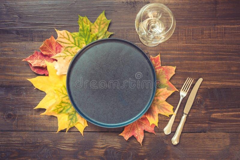 Πίνακας φθινοπώρου και ημέρας των ευχαριστιών που θέτει με τα πεσμένα φύλλα, τα καρυκεύματα, το μαύρες πιάτο και τις ασημικές στο στοκ φωτογραφία με δικαίωμα ελεύθερης χρήσης