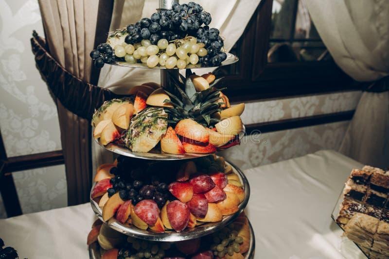Πίνακας φρούτων στη δεξίωση γάμου με το μοντέρνο ντεκόρ, φρούτα και στοκ φωτογραφία