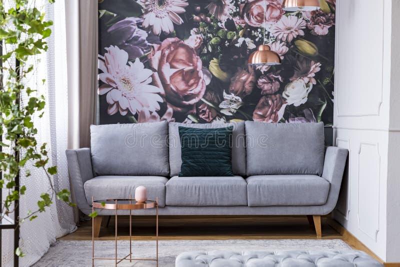 Πίνακας χαλκού στον τάπητα και πράσινο μαξιλάρι στον γκρίζο καναπέ στα λουλούδια στοκ εικόνες