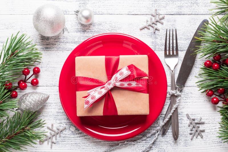 Πίνακας Χριστουγέννων που θέτει με το κόκκινο πιάτο, το κιβώτιο δώρων και τις ασημικές στο ελαφρύ ξύλινο υπόβαθρο Κλάδος δέντρων  στοκ εικόνες