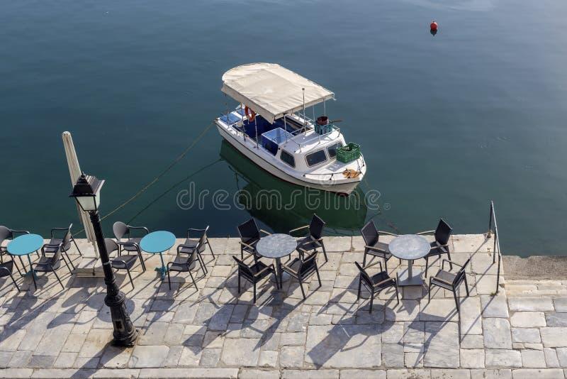 Πίνακες και καρέκλες ενός καφέ Ελλάδα, Πελοπόννησος οδών στοκ εικόνες