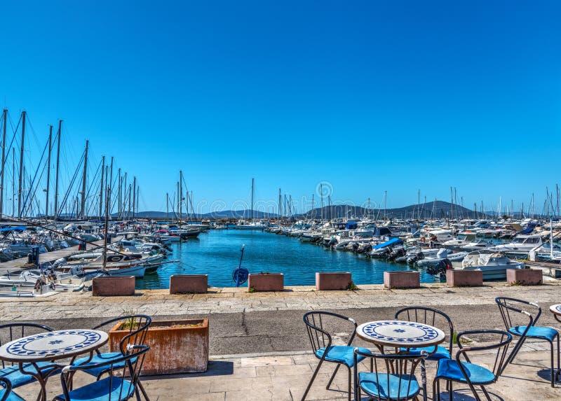 Πίνακες και καρέκλες από Alghero το λιμάνι στοκ εικόνες