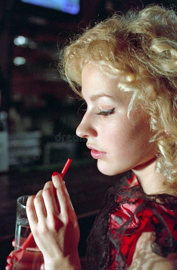 Πίνοντας κορίτσι στο αναδρομικό συμβαλλόμενο μέρος στοκ εικόνες
