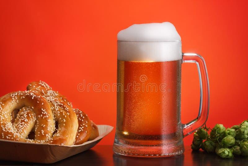 Πίντα της μπύρας με τα συστατικά για τη σπιτική μπύρα στο κόκκινο με pretzel στοκ εικόνα