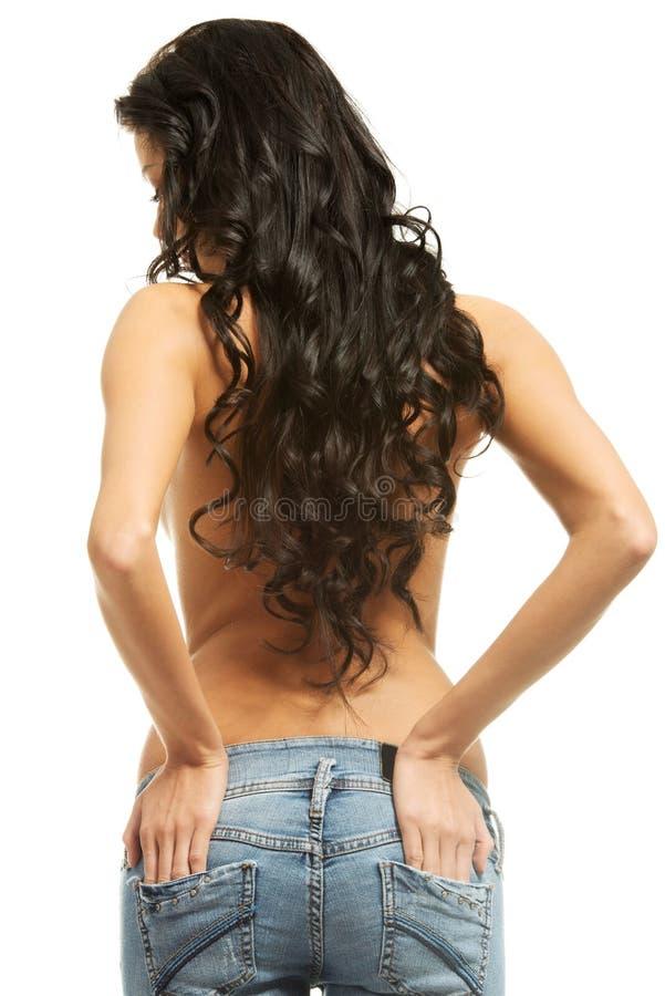Πίσω άποψη ενός γυμνοστήθου γυναικών που φορά τα τζιν στοκ εικόνες με δικαίωμα ελεύθερης χρήσης