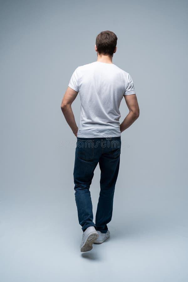 Πίσω άποψη ενός περιστασιακού νεαρού άνδρα που περπατά και που κοιτάζει στην πλευρά στο γκρίζο υπόβαθρο στοκ φωτογραφία με δικαίωμα ελεύθερης χρήσης