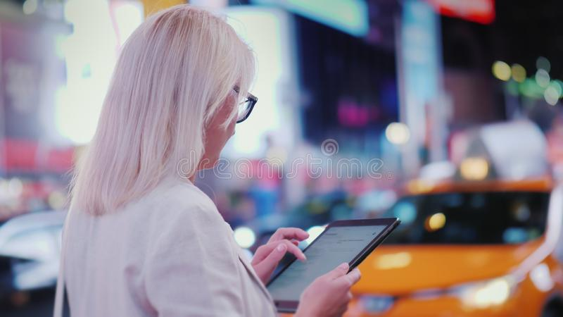 Πίσω άποψη: Η επιχειρησιακή γυναίκα χρησιμοποιεί την ταμπλέτα στην πολυάσχολη Times Square στη Νέα Υόρκη Τα διάσημα κίτρινα αμάξι στοκ φωτογραφία με δικαίωμα ελεύθερης χρήσης
