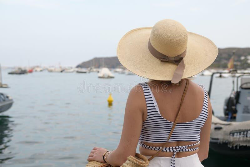Πίσω άποψη μιας γυναίκας που εξετάζει τη θάλασσα πέρα από τον περίπατο παραλιών στοκ εικόνες με δικαίωμα ελεύθερης χρήσης