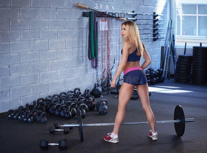 Πίσω άποψη μιας φίλαθλης γυναίκας ικανότητας με ένα μυϊκό σώμα sportswear που κάνει την άσκηση με ένα barbell σε μια γυμναστική στοκ φωτογραφία με δικαίωμα ελεύθερης χρήσης