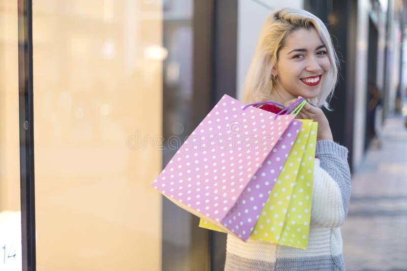 Πίσω άποψη μιας χαμογελώντας νέας γυναίκας που στέκεται και που κρατά τις τσάντες καταστημάτων κοιτάζοντας πίσω στη κάμερα σε ένα στοκ φωτογραφία με δικαίωμα ελεύθερης χρήσης