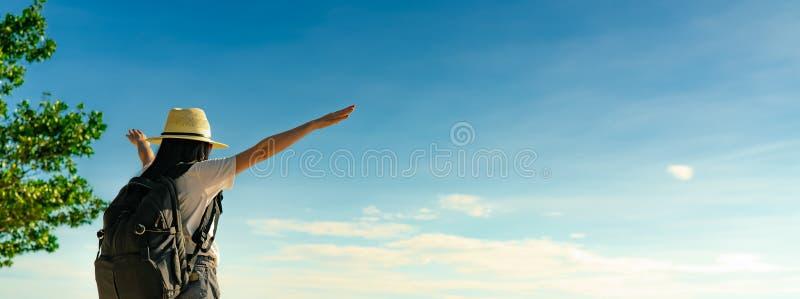 Πίσω άποψη της ευτυχούς νέας ασιατικής γυναίκας στην περιστασιακή μόδα ύφους με το καπέλο αχύρου και το σακίδιο πλάτης Χαλαρώστε  στοκ εικόνες
