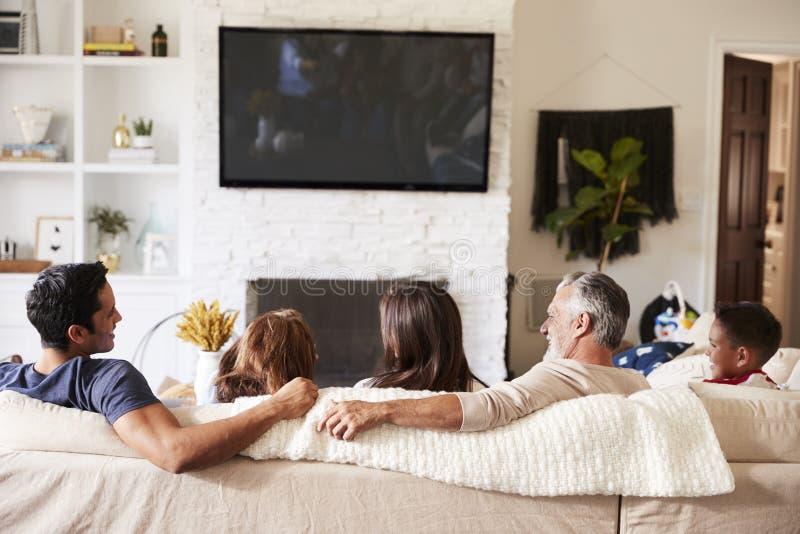 Πίσω άποψη της ισπανικής οικογένειας τριών γενεάς στον καναπέ που προσέχει τη TV, grandad εξετάζοντας τον ενήλικο γιο στοκ εικόνες