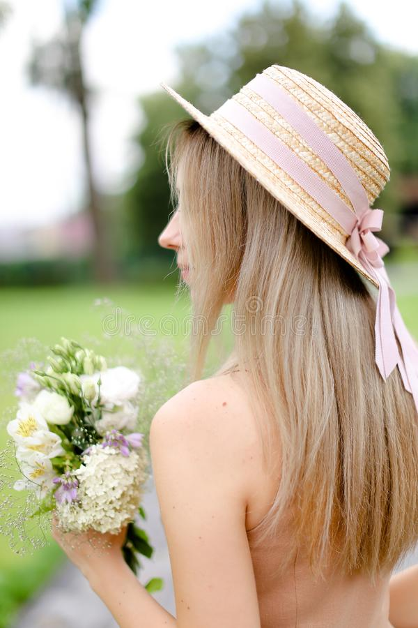 Πίσω άποψη της νέας ξανθής γυναίκας στις φόρμες χρώματος σωμάτων και του καπέλου με τα λουλούδια στοκ εικόνες